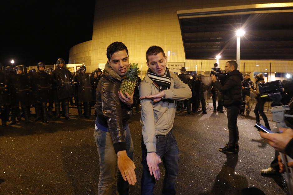 """Jóvenes hacen el gesto """"quenelle"""" fuera de la sala de conciertos en Nantes, donde un espectáculo prohibido del humorista francés Dieudonné M'bala M'bala, también conocido como Dieudonné, estaba previsto para el 9 de enero de 2014. Los críticos dicen que la marca registrada del cómico, el brazo recto, es un saludo nazi a la inversa. Dieudonné, de 46 años, dice que es anti-sionista y anti-sistema, pero no antisemita. Stephane Mahe / Reuters"""