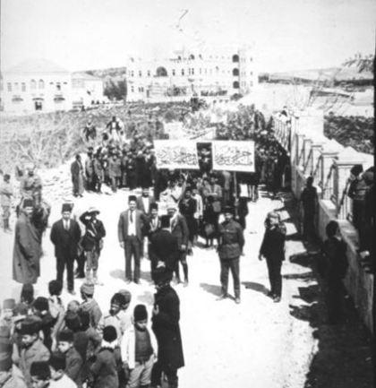 """Manifestación árabe en Jerusalén, alrededor de 1920. El cartel de la izquierda dice: """"Resistimos a la inmigración judía"""", el de la derecha: """"Palestina es parte de Siria""""."""