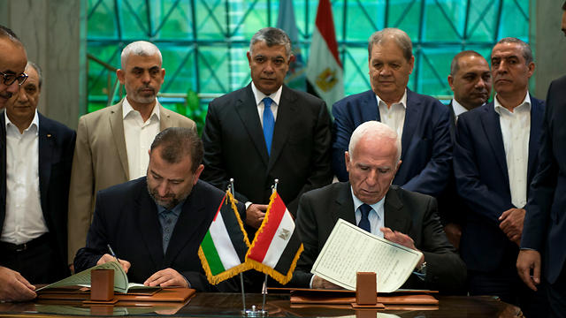 Sinwar watches as senior Fatah official Azzam al-Ahmad (R) and Hamas deputy politburo chief Saleh al-Arouri sign a reconciliation deal in Cairo last Thursday (Photo: EPA)