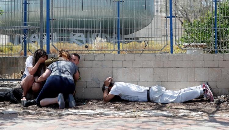 Los israelíes se esconden mientras escuchan sirenas que advierten de la llegada de cohetes desde Gaza, durante las hostilidades transfronterizas, en la ciudad israelí de Ashkelon, al sur del país, el 5 de mayo de 2019. (REUTERS)
